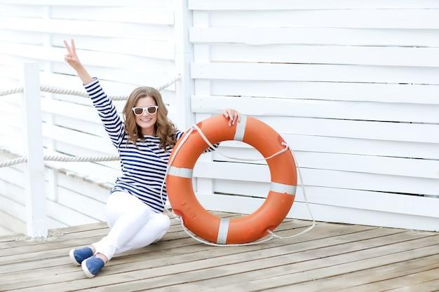 Ragazza sexy contro la parete di legno sotto forma di marinai con un'ancora di salvezza e un cappuccio.