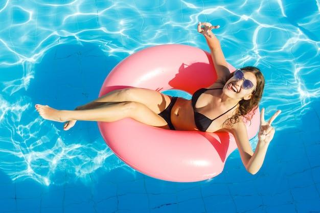 Ragazza sexy divertendosi e ridendo su un anello rosa gonfiabile. donna in piscina