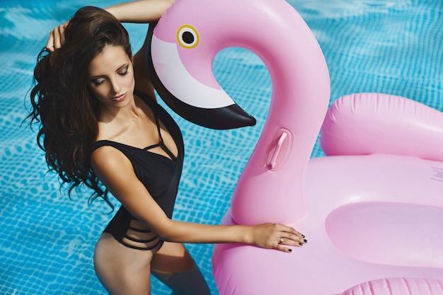 Ragazza sexy e alla moda del brunette con il fenicottero rosa nella piscina
