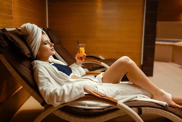 Ragazza sexy in accappatoio e asciugamano sulla testa rilassante con un cocktail sulla sedia spa.