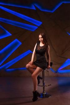 Ragazza sexy in un vestito nero su uno sgabello da bar