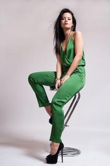Ragazza sexy vestita di moda che si siede sulla sedia