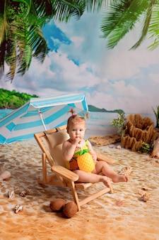 Ragazza si trova su una sedia a sdraio, prende il sole su una spiaggia sabbiosa con palme in riva al mare e beve succo di frutta