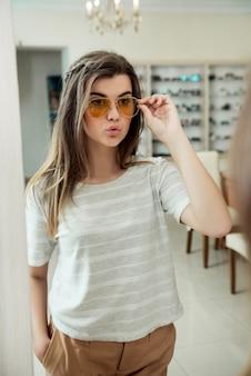 Ragazza sicura attraente che prova sugli occhiali alla moda mentre sull'acquisto nel deposito dell'ottico