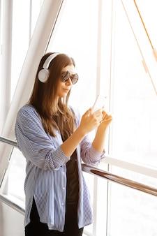 Ragazza sicura o free lance in cuffie che ascoltano la musica, esaminante il telefono mentre nella stanza, aeroporto, ufficio. telefono cellulare nelle mani delle giovani donne alla moda alla moda con gli occhiali.
