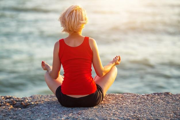 Ragazza snella con i capelli corti che si siede sulla spiaggia che medita al tramonto