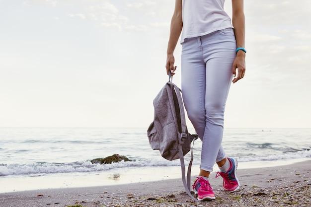 Ragazza snella in jeans e scarpe da ginnastica, camminando lungo la spiaggia di sera con uno zaino
