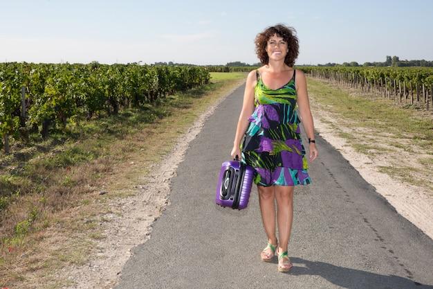 Ragazza sola con la valigia alla strada campestre