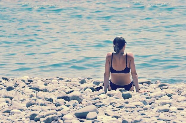 Ragazza sola in bikini e berretto da baseball che si siedono su una spiaggia di pietra