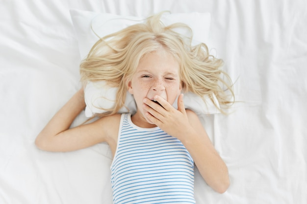 Ragazza sonnolenta che si sveglia presto al mattino, coprendosi la bocca con la mano mentre sbadiglia, va a scuola o all'asilo. bionda affascinante bambino in marinaio t-shirt sdraiata sul letto bianco vestiti, appena sveglio