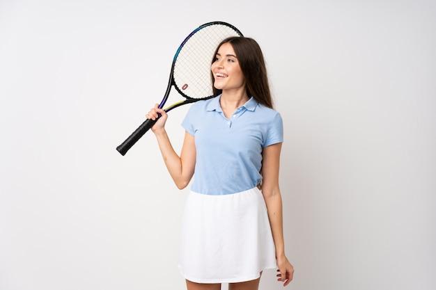 Ragazza sopra la parete bianca isolata che gioca a tennis e che osserva in su