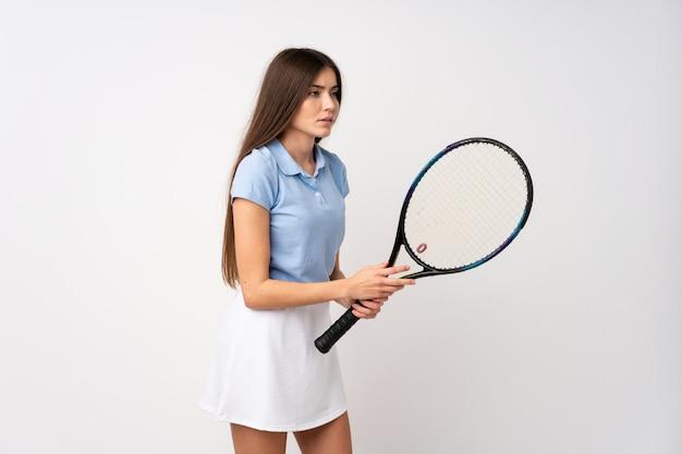 Ragazza sopra la parete bianca isolata che gioca a tennis