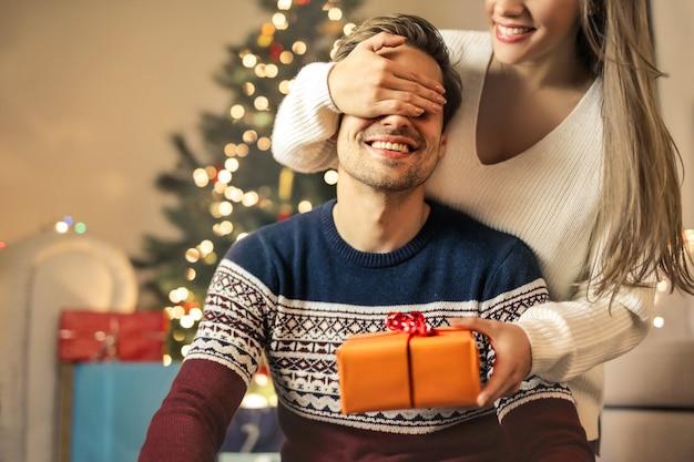Ragazza sorprendente il suo ragazzo con un regalo di natale