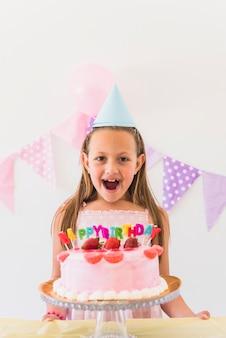 Ragazza sorpresa allegra di compleanno che si leva in piedi dietro la torta e le candele