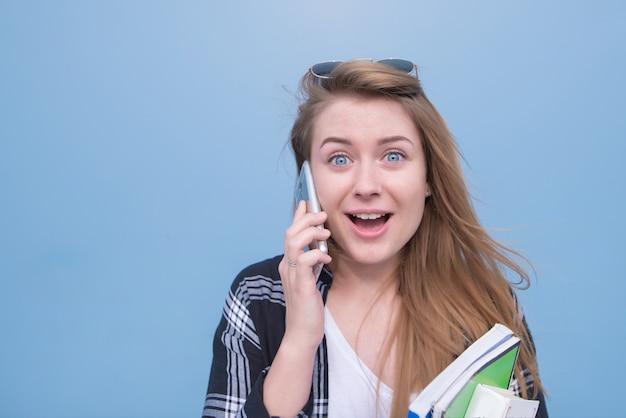 Ragazza sorpresa che parla sul telefono e che esamina la macchina fotografica su un fondo blu.