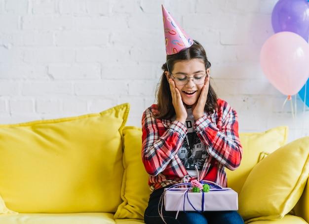 Ragazza sorpresa che si siede sul sofà con il regalo di compleanno