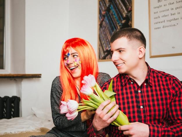 Ragazza sorpresa con i capelli rossi e tulipani della tenuta del ragazzo