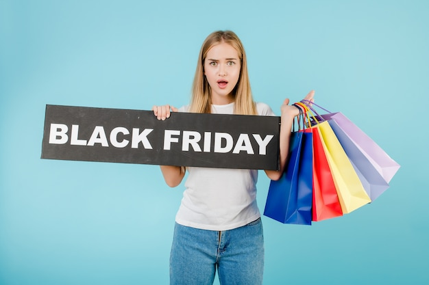 Ragazza sorpresa con il segno di venerdì nero e sacchetti della spesa variopinti isolati sopra il blu