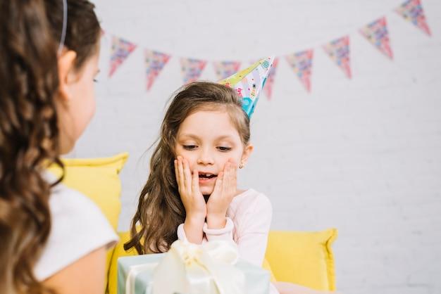 Ragazza sorpresa di compleanno che guarda attualmente comprata dalla sua amica