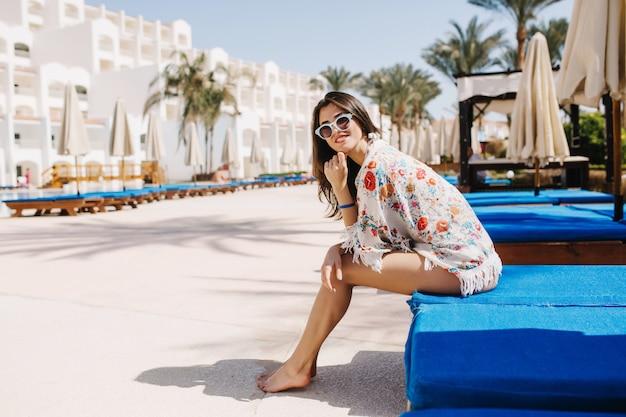 Ragazza sorridente a piedi nudi in vestiti alla moda che si siedono sulla chaise-longue blu e che godono del sole tropicale. adorabile giovane donna che ride in occhiali da sole che riposa fuori con le palme