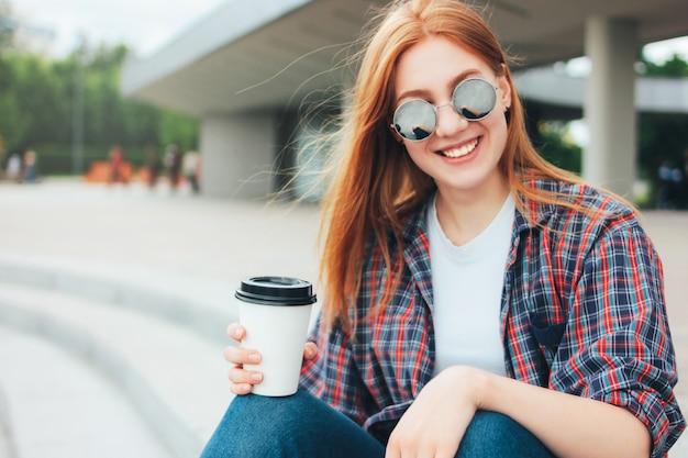 Ragazza sorridente attraente rossa in occhiali da sole rotondi con una tazza di caffè per andare nelle mani