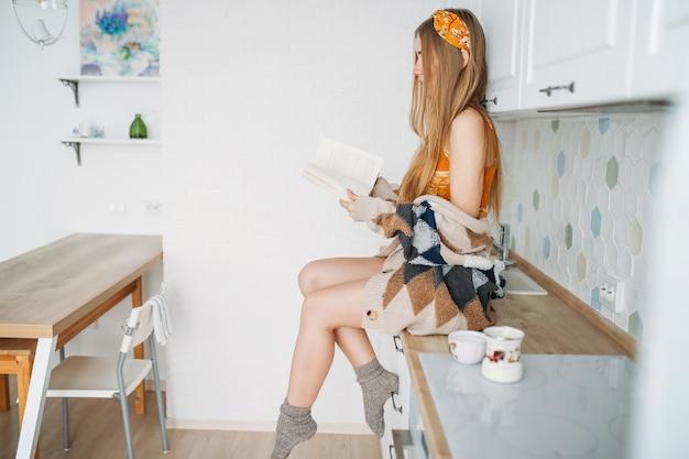 Ragazza sorridente bella dei capelli lunghi della giovane donna sorridente che indossa in libro di lettura tricottato accogliente del cardigan che si siede sulla superficie di lavoro della cucina a casa