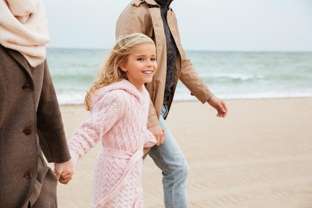 Ragazza sorridente che cammina con i suoi genitori