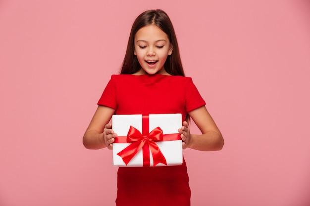 Ragazza sorridente che esamina regalo in mani e sorridere isolato