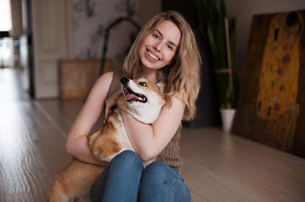 Ragazza sorridente che gioca con il suo cucciolo di welsh corgi pembroke, cane sveglio felice