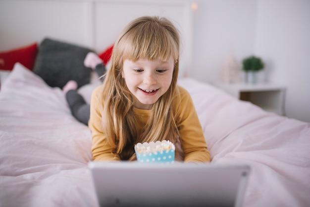 Ragazza sorridente che guarda film sul tablet