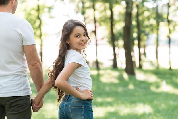 Ragazza sorridente che guarda l'obbiettivo mentre si cammina nel parco con suo padre