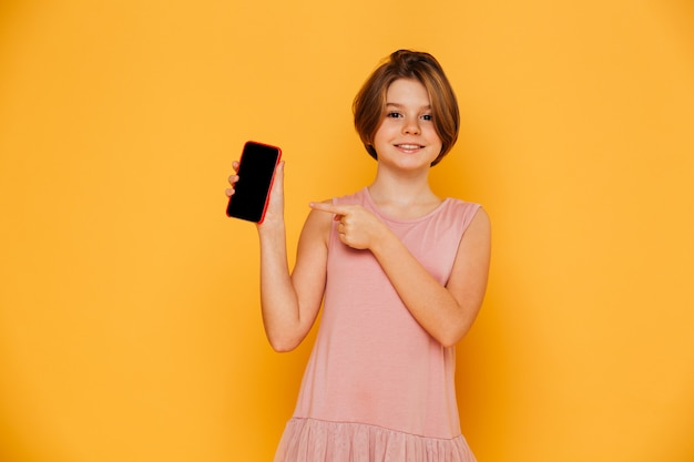 Ragazza sorridente che indica allo schermo in bianco dello smartphone isolato