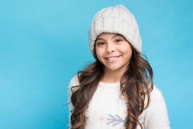 Ragazza sorridente che indossa cappello bianco e vestiti su sfondo blu