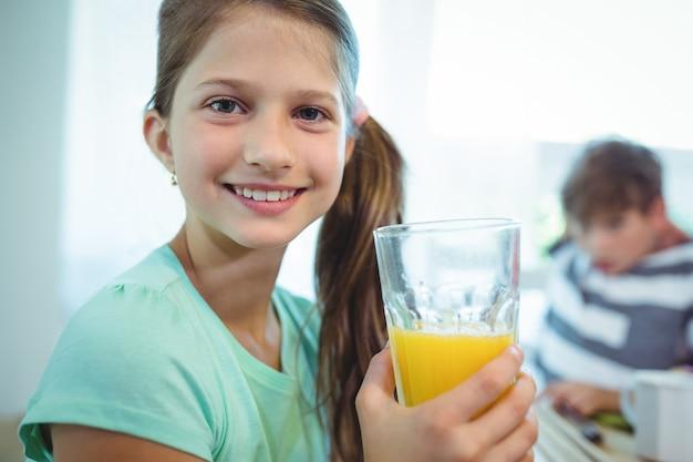 Ragazza sorridente che mangia il succo di arancia