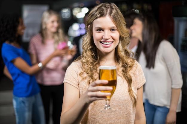Ragazza sorridente che mangia una birra con i suoi amici