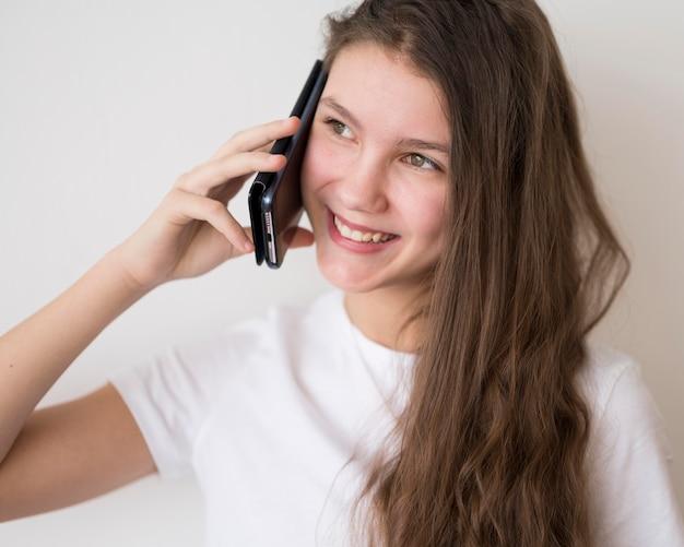 Ragazza sorridente che parla sopra i telefoni