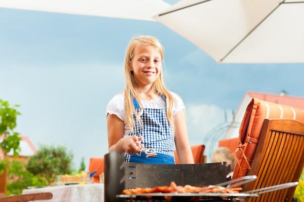 Ragazza sorridente che posa con la griglia del barbecue