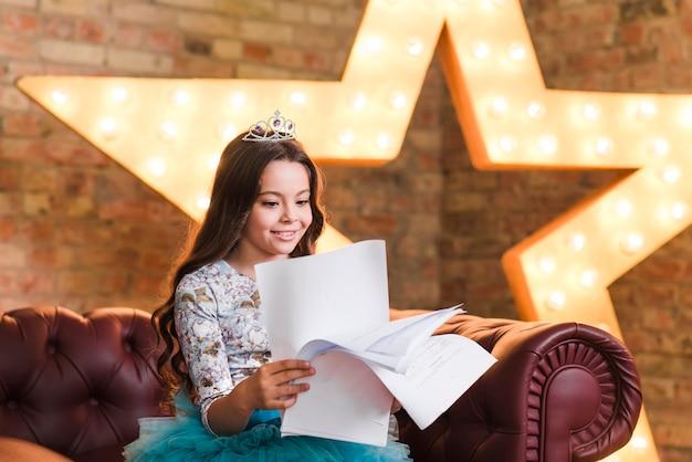 Ragazza sorridente che si siede sugli scritti della lettura del sofà contro la stella d'ardore nella priorità bassa