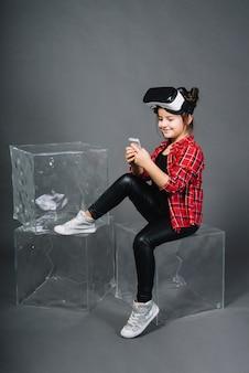 Ragazza sorridente che si siede sul blocco facendo uso del telefono cellulare che si siede contro il contesto grigio