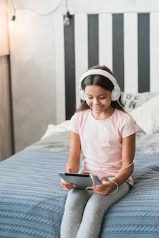 Ragazza sorridente che si siede sulla musica d'ascolto del letto sulla cuffia