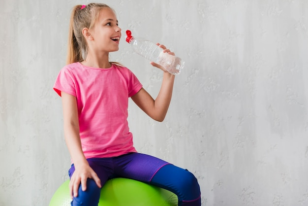 Ragazza sorridente che si siede sulla palla verde dei pilates che beve l'acqua dalla bottiglia contro il muro di cemento