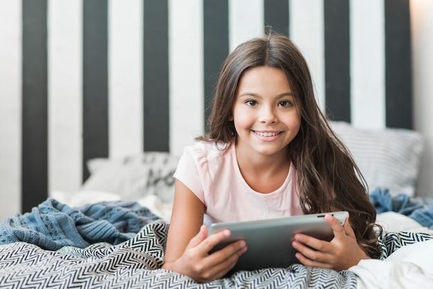 Ragazza sorridente che si trova sul letto sudicio con tavoletta digitale