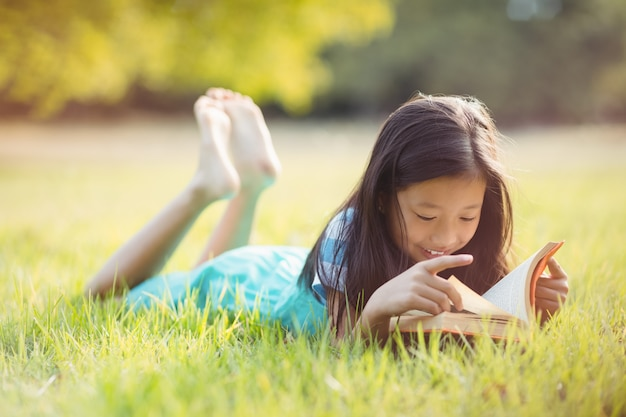 Ragazza sorridente che si trova sull'erba e sul libro di lettura in parco
