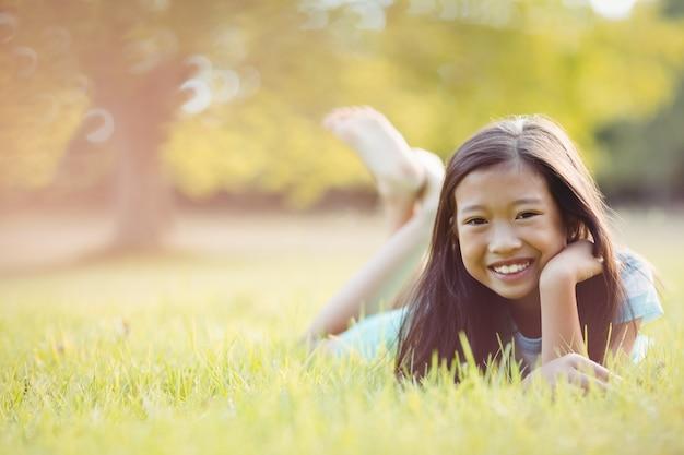 Ragazza sorridente che si trova sull'erba