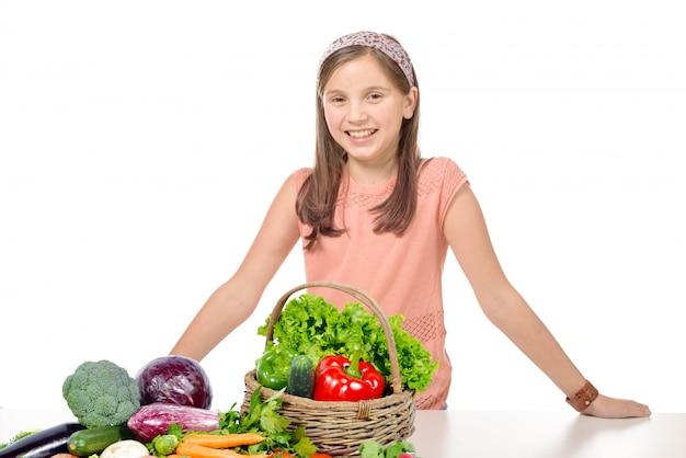 Ragazza sorridente che sta dietro le verdure di un mucchio