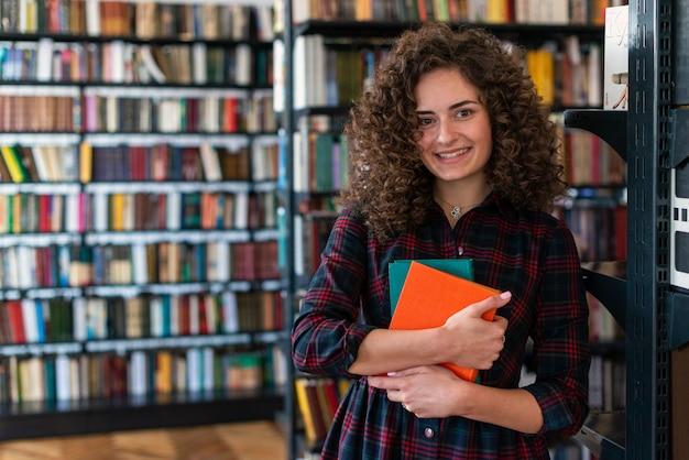 Ragazza sorridente che sta nella biblioteca che abbraccia i libri in sue mani