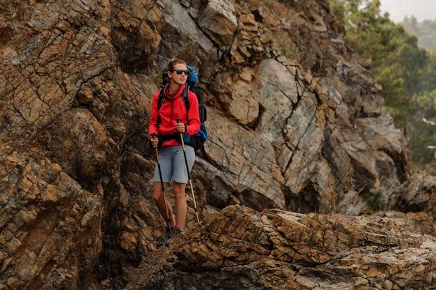 Ragazza sorridente che sta sulle rocce con l'escursione dello zaino e dei bastoni da passeggio