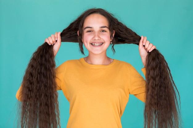 Ragazza sorridente che tiene i suoi capelli lunghi