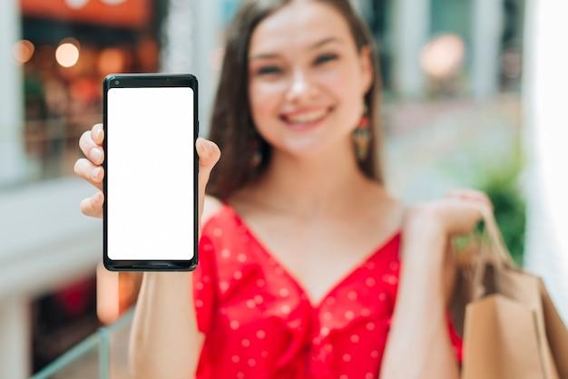 Ragazza sorridente che tiene il suo telefono