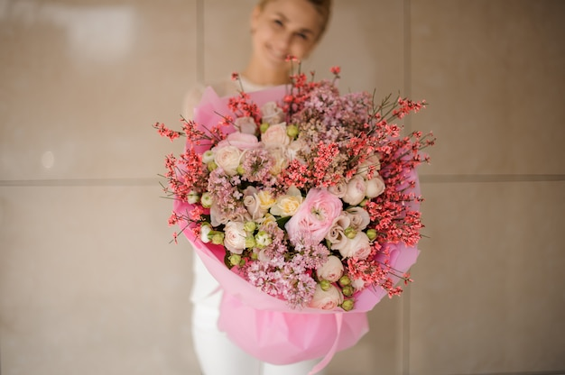 Ragazza sorridente che tiene un mazzo della molla di colore rosa tenero e dei fiori bianchi